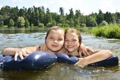 Twee meisjesmeisjes op de zomermeer die in het meer zwemmen en sm royalty-vrije stock afbeelding