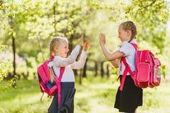 Twee meisjesschoolmeisje met roze rugzak en spel pasteitje-Cake in openlucht royalty-vrije stock foto's