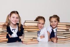 Twee meisjesschoolmeisjes zitten met boeken bij zijn bureau op de les op school stock foto