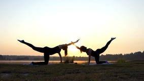Twee Meisjestribune op Al Fours op een Yogamat op een Meerbank bij Zonsondergang stock video