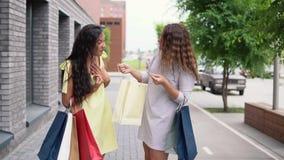 Twee meisjesvrienden bespreken het winkelen na het winkelen Langzame Motie stock videobeelden