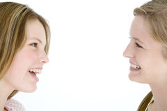 Twee meisjesvrienden die elkaar bekijken het glimlachen Royalty-vrije Stock Foto's