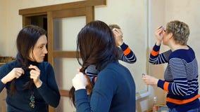 Twee meisjesvrienden die in het kleden van make-upruimte roddelen Royalty-vrije Stock Afbeelding