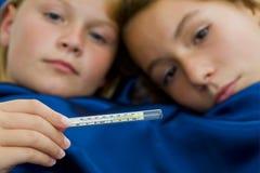 Twee meisjeszieken in bed Stock Afbeelding