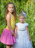 Twee meisjeszuster het stellen in stadspark, kinderjarenconcept, gelukkig kindportret Royalty-vrije Stock Afbeelding
