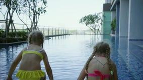 Twee meisjeszusters gaan zitten dichtbij de panoramische pool, achtermening, langzame motie stock video