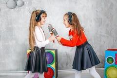 Twee meisjevrienden zingen en dansen Het concept is kinderjaren Royalty-vrije Stock Foto's