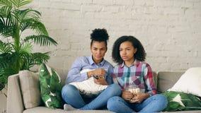 Twee mengden vrienden die van het ras de krullende meisje op de laag en horloge zeer enge film op TV zitten en eten thuis popcorn stock afbeeldingen