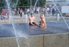 Twee mensen beklommen in de fontein om aan de hitte te ontsnappen Royalty-vrije Stock Afbeelding