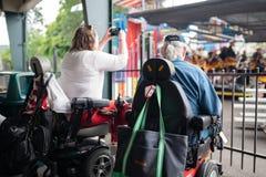 Twee mensen bij rolstoelen genieten van overleggen in openlucht royalty-vrije stock foto