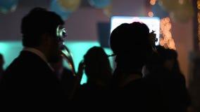Twee mensen binnen publiek dansen terug naar camera, mens en vrouw die zich aan de muziek met maskerademaskers de bewegen op hun stock videobeelden
