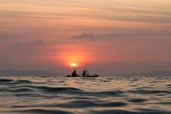 Twee mensen in de boot tegen een zonsondergang Stock Afbeeldingen