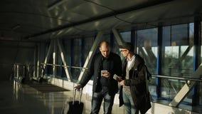 Twee mensen in de gang van de luchthaven in afwachting van het begin van registratie mee te delen stock videobeelden