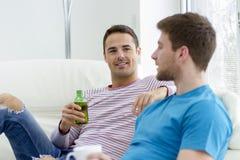 Twee Mensen die Bier thuis drinken stock fotografie