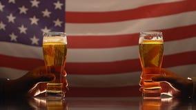 Twee mensen die bierglazen, Amerikaanse vlag op achtergrond houden, die in bar gelijk maken stock videobeelden