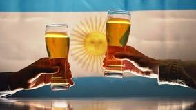 Twee mensen die bierglazen clinking tegen achtergrond met Argentijnse vlag, langzaam-mo stock footage