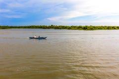 Twee Mensen die een Boot varen omhoog de Rivier langs Overstroomd Forest Line Stock Afbeeldingen