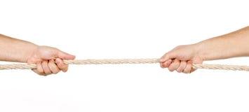 Twee mensen die een kabel in tegenovergestelde geïsoleerdee richtingen trekken Stock Foto