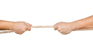 Twee mensen die een kabel in tegenovergestelde geïsoleerdee richtingen trekken Stock Foto's