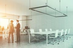 Twee mensen die in een witte bureauvergaderzaal spreken Stock Foto's
