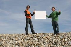 Twee Mensen die een witte kaart houden Stock Foto's