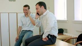 Twee mensen die gesprek telefonisch mobiel in school of universiteit hebben stock video