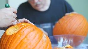 Twee mensen die Halloween-pompoenen snijden stock videobeelden