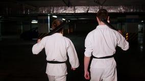 Twee mensen die in kimono op een parkeerterrein lopen die een opleidingszwaarden op hun schouders houden stock footage