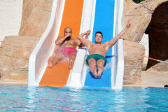 Twee mensen die onderaan een water dia-vrienden berijden die van een rit van de waterbuis genieten Stock Foto's