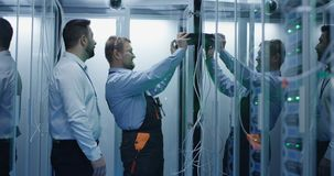 Twee mensen die onderhoud in een datacentrum uitvoeren stock video