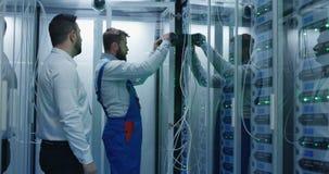 Twee mensen die onderhoud in een datacentrum uitvoeren stock footage