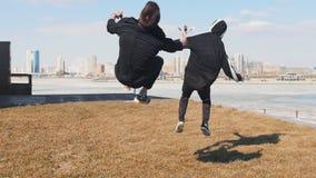 Twee mensen die op het gras lopen en een tik uitvoeren stock videobeelden