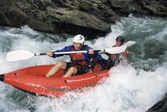 Twee mensen die opblaasbare boot onderaan stroomversnelling paddelen Stock Foto's
