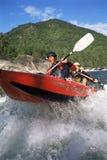 Twee mensen die opblaasbare boot onderaan stroomversnelling paddelen royalty-vrije stock foto's