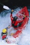Twee mensen die opblaasbare boot onderaan stroomversnelling paddelen Royalty-vrije Stock Afbeeldingen
