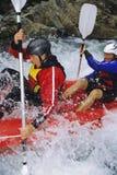 Twee mensen die opblaasbare boot onderaan stroomversnelling paddelen Royalty-vrije Stock Foto