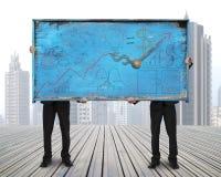 Twee mensen die oud blauw krabbelsaanplakbord op wolkenkrabbercitysca houden Stock Fotografie