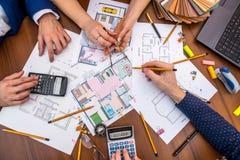 Twee mensen die over architecturaal project met techniekhulpmiddelen op werkplaats spreken royalty-vrije stock afbeeldingen