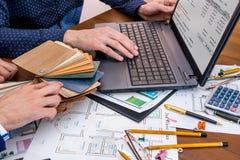 Twee mensen die over architecturaal project met techniekhulpmiddelen op werkplaats spreken royalty-vrije stock afbeelding