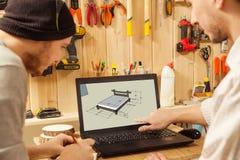 Twee mensen die schets van houten bed op laptop bekijken stock afbeeldingen