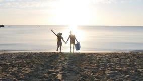 Twee mensen die speelse holdingshanden op de vakantie van de de zomerreis in werking stellen stock video