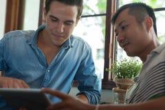 Twee Mensen die Tablet, Aziatische de Vriendenkerels gebruiken van het Mengelingsras royalty-vrije stock afbeeldingen