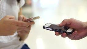 Twee mensen die touchscreen slimme telefoon in publiek met behulp van Close-up van handen die op twee apparaten typen De maatscha stock footage