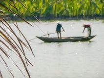 Twee mensen die traditionele Vietnamese kleding dragen die een boot binnen roeien Royalty-vrije Stock Afbeelding