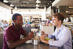 Twee Mensen die van Lunch in Delicatessenrestaurant genieten stock foto's