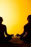 Twee mensen die yoga in het zonsonderganglicht uitoefenen Royalty-vrije Stock Foto