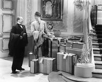 Twee mensen die zich in de gang met vele koffers bevinden (Alle afgeschilderde personen leven niet langer en geen landgoed bestaa Royalty-vrije Stock Fotografie
