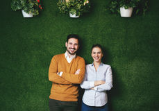 Twee mensen die zich over een groene grasmuur bevinden royalty-vrije stock fotografie