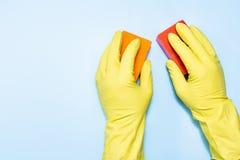 Twee mensen dient rubberhandschoenen met spons op een blauwe achtergrond in stock afbeeldingen
