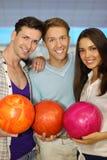 Twee mensen en meisjesgreepballen in kegelenclub Stock Foto's